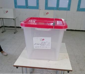 Urne pour les législatives en Tunisie. Derrière, les isoloirs électoraux sont en carton.