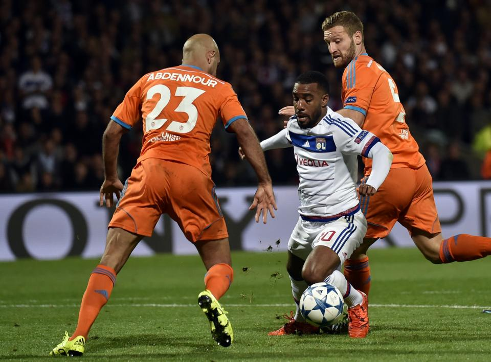 Lyon's French forward Alexandre Lacazette (C) vies for the ball with Valencia's Tunisian defender Aymen Abdennour (L) and Valencia's German defender Shkodran Mustafi (R) during the Champions League group H football match between Lyon and Valencia on September 29, 2015 at the Gerland stadium in Lyon, central-eastern France. AFP PHOTO / JEFF PACHOUD
